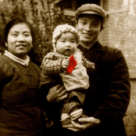 "My dad was sent to Xichang, an outpost, to ""reform"" and ""serve the people"" when I was born. Dad saw me, his firstborn, for the first time when I was a seven-month-old. The Little Red Book in my hand served as the standard photo pop and rattle for a baby. I looked a little rattled—the photographer was shining too much light on me with a rice-bowl-sized Mao pin."